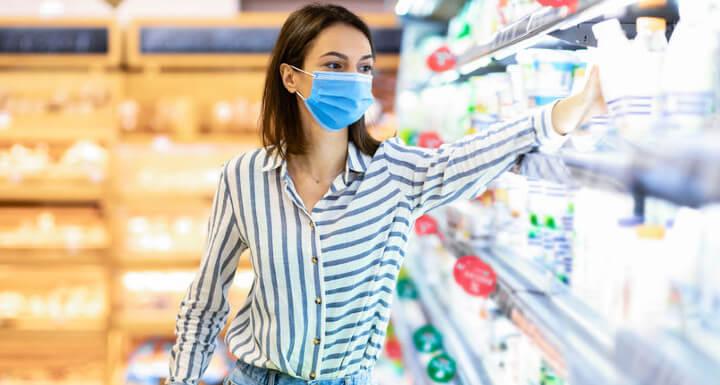 mujer cogiendo un producto de los estantes del supermercado
